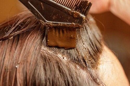Mujer aplicándose en el cabello tinte de henna