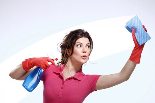 A woman cleaning glass with a sponge