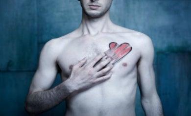 Chico tocandose el pecho borrando un corazón pintado