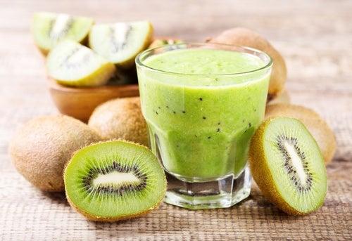 Kiwi smoothie surrounded by kiwi cut
