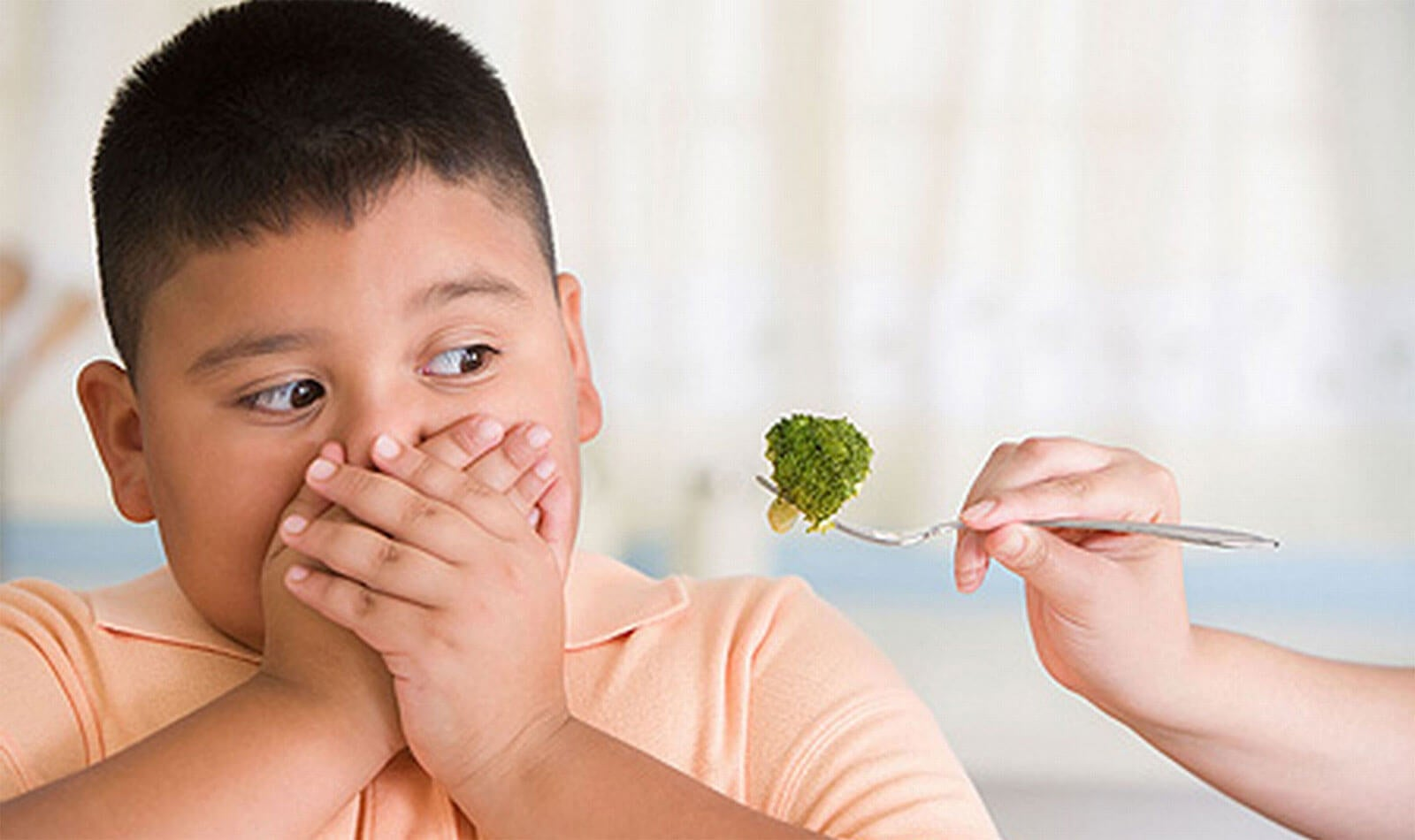 Niño obeso rechazando brócoli