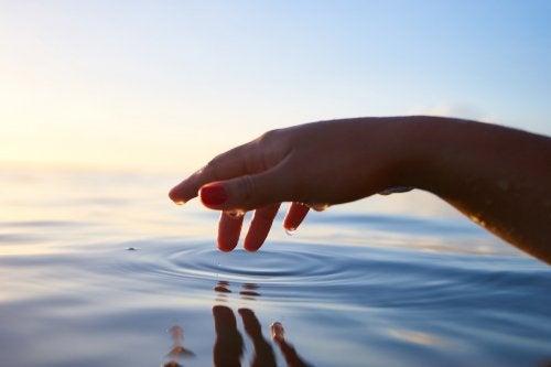 manos tocando agua