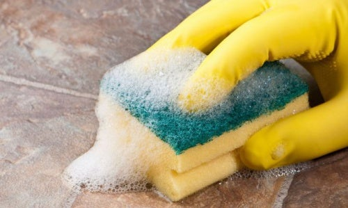 Mujer limpiando superficie con guantes