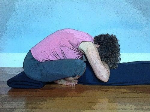 Mujer realizando la postura de recogimiento interno