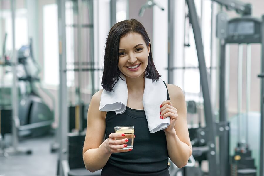 Mujer en el gimnasio con una bebida en mano.