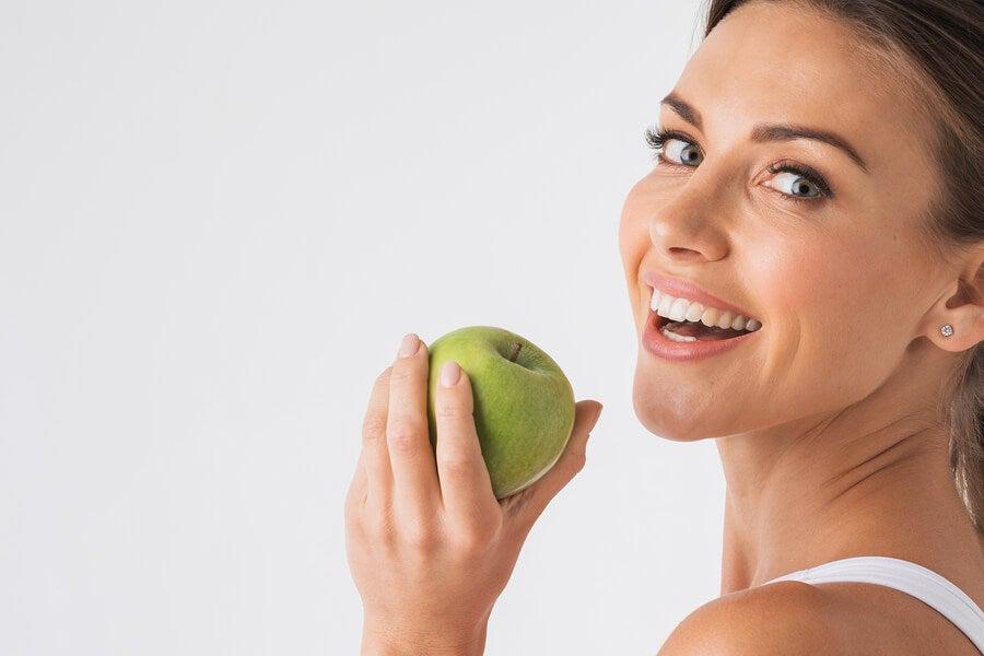 Mujer sonriendo con una manzana verde en la mano.