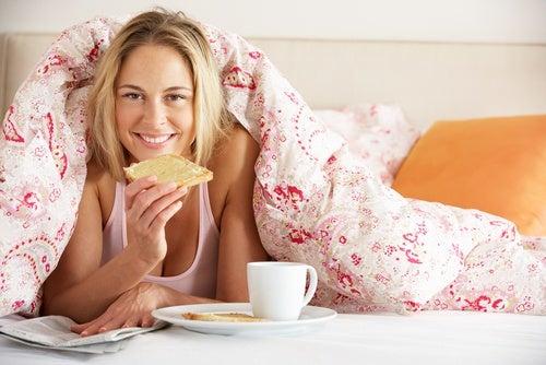 Mujer sobre la cama con el desayuno