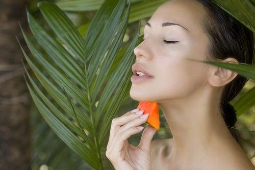 Mujer aplicándose un trozo de papaya sobre la piel