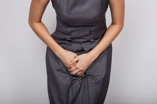 Mujer aguántandose las ganas de orinar provocadas por la vejiga hiperactiva