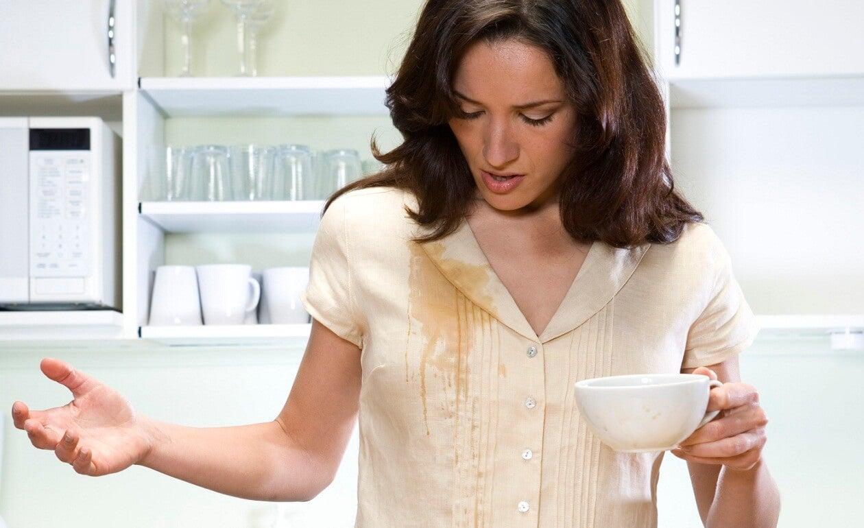 Mujer con una mancha de café en la ropa