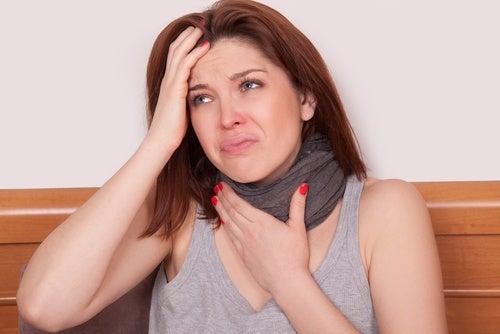 Mujer tocándose el cuello por molestias de la garganta