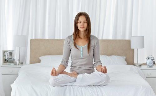 Mujer sentada en la cama meditando