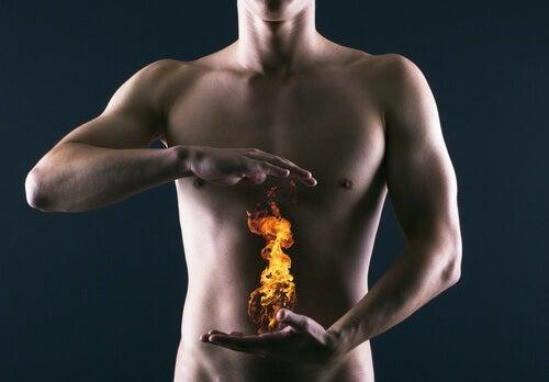 Hombre con fuego en el estómago representando la acidez estomacal.