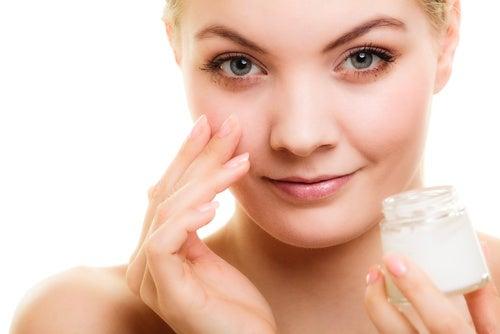 mujer aplicando crema antiarrugas en el rostro