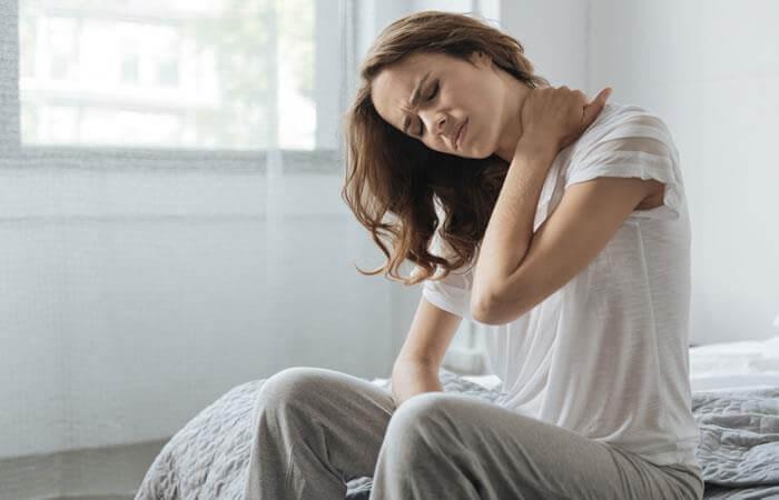 Mujer levantándose de la cama con torticolis