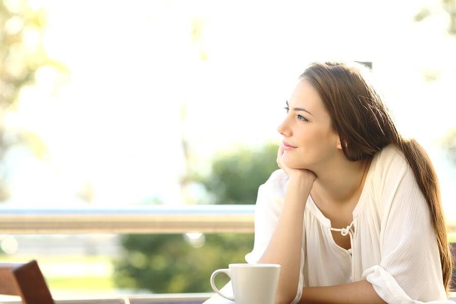 Mujer pensativa en medio de una reflexión positiva.