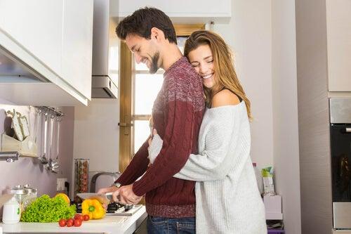 Chica abrazando a su pareja en la cocina.