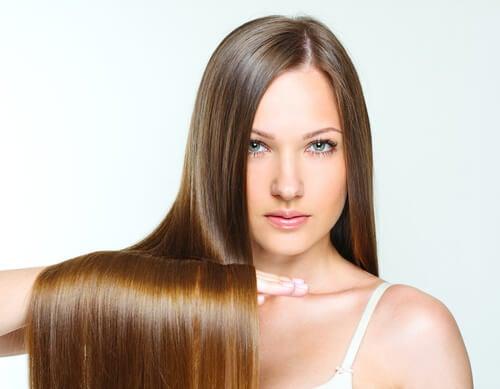 Mujer con pelo lacio largo y brillante gracias a la mascarilla natural que se ha aplicado