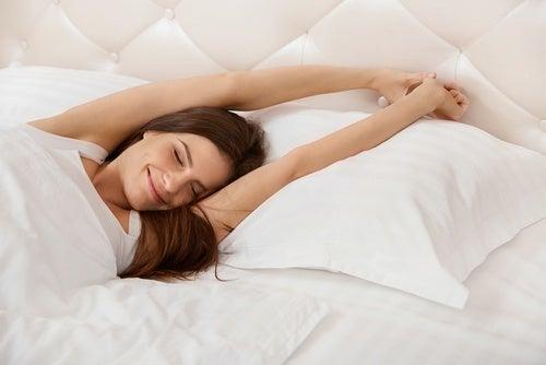 Mujer despertándose contenta en la cama