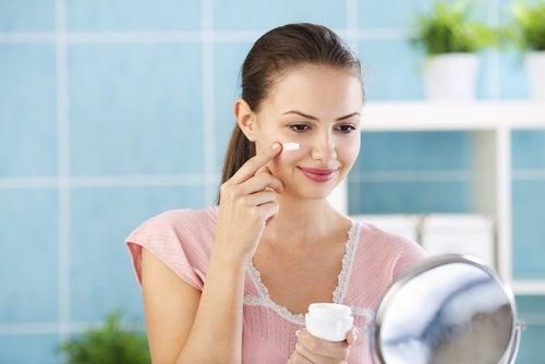 Mujer echándose crema en el rostro
