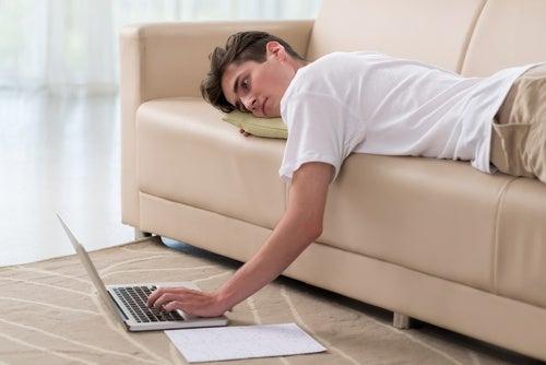Chico consultando el ordenador desde el sofá