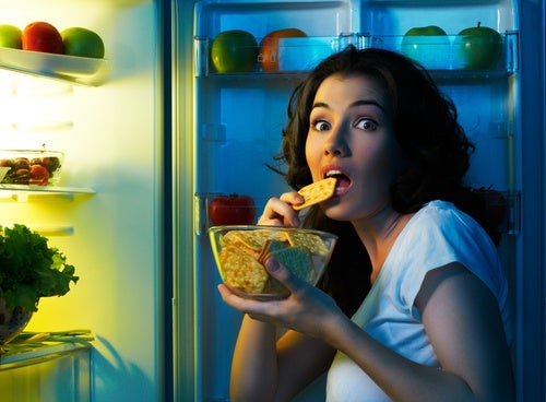 Chica comiendo del frigorífico