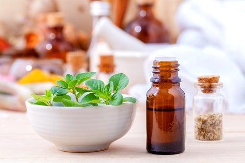 Aceite de orégano junto a un bol con hojas de la planta