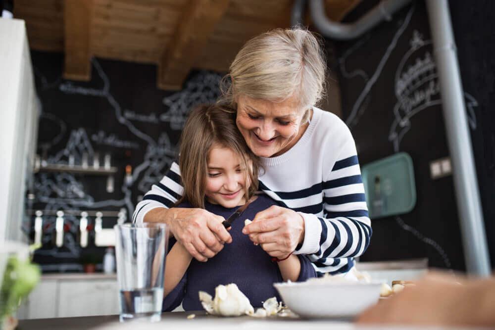 Abuela enseñando a cocinar a su nieta.