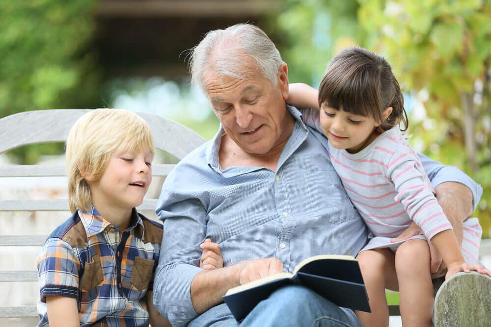 Abuelo leyendo con los nietos.