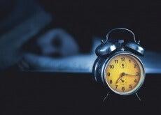 despertador y hombre acostado