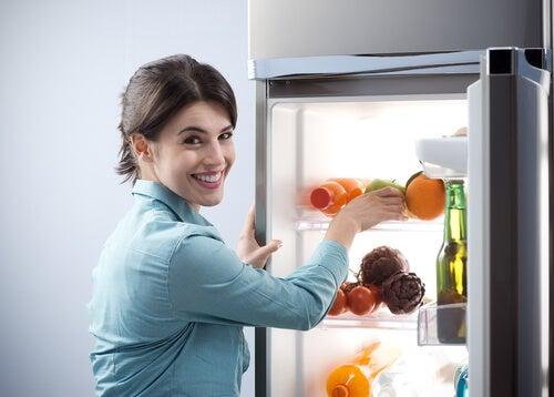 mujer guardando alimentos en la nevera para que la comida dure más