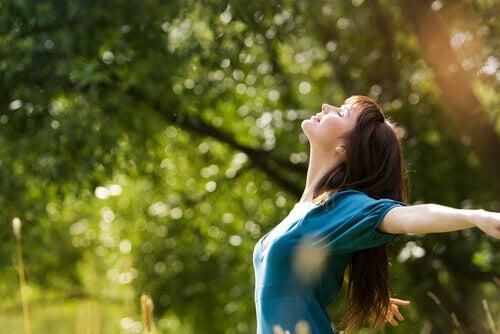 Mujer feliz abriendo los brazos bajo el sol.