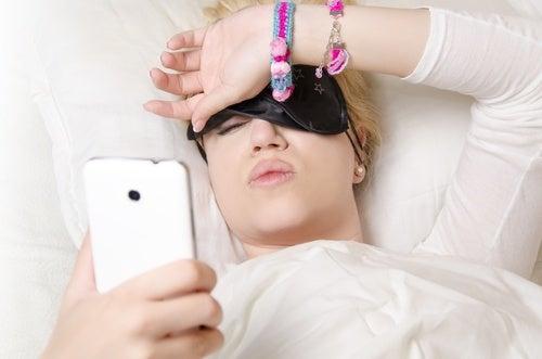 mujer en la cama mirando el móvil