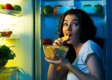Mujer comiendo del frigorifico
