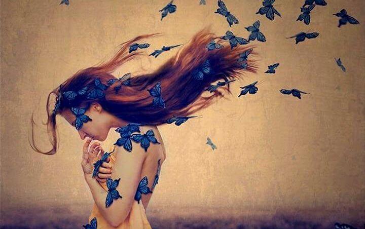 mujer con mariposas azules en el cabello