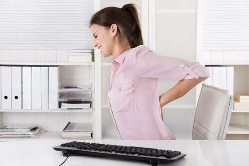 Mujer con dolor de espalda en oficina.