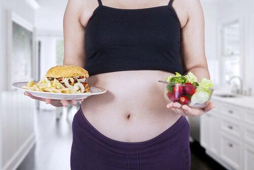 Mujer embarazada con comida buena y mala.