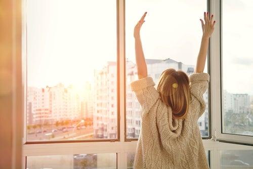 Mujer de espaldas con brazos levantados
