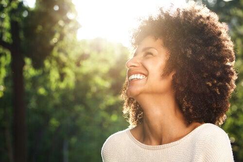 Mujer sonriendo al aire libre.