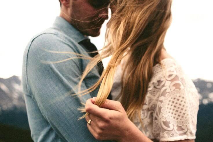 pareja abrazada dándose una caricia