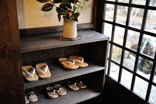 Zapatos en un estante a la entrada de la casa