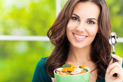Mujer con un bol de frutas y verduras. Alimentación equilibrada entre los hábitos saludables para potenciar la fertilidad.