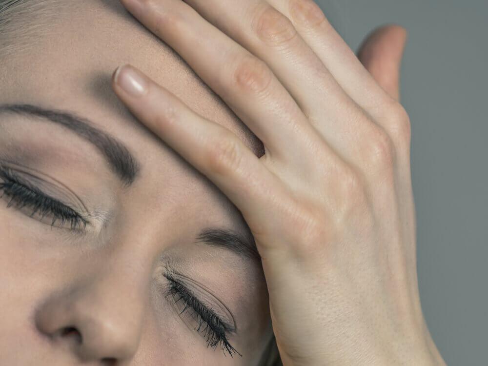 mujer con la mano en el rostro por dolor de cabeza.