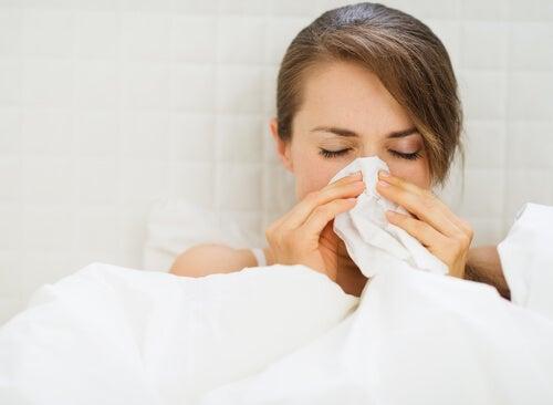 Mujer con catarro se suena la nariz