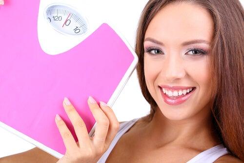 Chica sonriendo con la báscula en la mano tras haber perdido peso por consumir quinoa