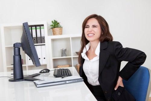 Mujer con dolor de espalda por estar sentada frente al ordenador
