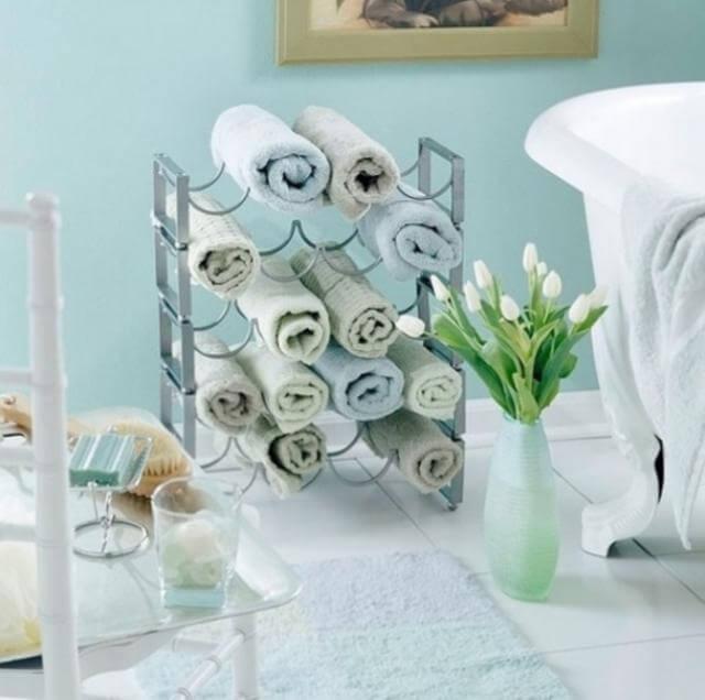 Utilizar un estante para vinos para acomodar toallas puede ayudar a tener un baño limpio y organizado