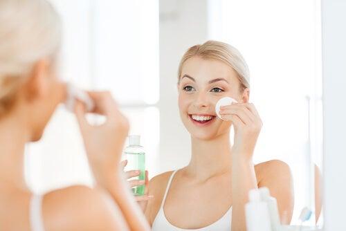 Mujer aplicándose un producto en la cara con un algodón.