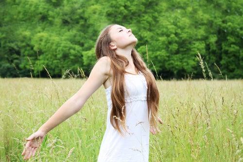 Mujer joven llenando sus pulmones de aire en una pradera.