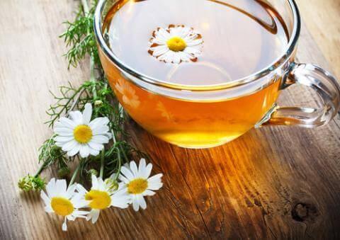 Taza con infusión de manzanilla y flores de manzanilla.